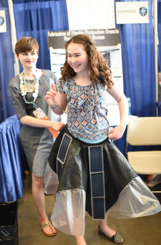 PITTSBURGH, Pa. May 14, 2015 - Allison Clausius, 18, of Toledo, Ohio, holds her cellphone charging dress at the waist of a young girl during the Intel International Science and Engineering Fair, the world's largest high school science competition. Approximately 1,700 high schoolers from 78 countries, regions and territories are competing for $4 million in awards this week. PHOTO CREDIT: Intel/Kathy Wolfe