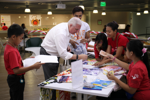 Wells Fargo Enterprise Global Services, LLC - Philippines Chief Administrative Officer Denis McGee buys handmade shirts from beneficiary school students during the Fundraising Week. (Photo: Business Wire)