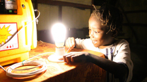 IEEE Smart Village and its partner Sirona Cares are working to put access to basic electricity into the homes of 1 million Haitian people; Haitian child excited by light provided from a personal battery kit (PBK). (Photo: Business Wire)