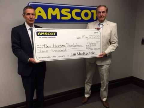 Ian MacKechnie, Amscot CEO and Founder, presents a check for $2000, accepted on behalf of Our Heroes Foundation by Richard Holland, formally a Special Agent with the FBI and now Amscot's VP of AML Compliance. (Photo: Business Wire)
