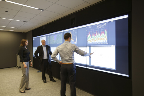 DMDII staff collaborating in the 'Connect Center', a room inside the new DMDII Innovation Institute in Chicago with an interactive touch screen that allows up to 10 individuals to connect simultaneously and collaborate on projects. Data streams in real time from machines in their Manufacturing Demonstration Lab. GE is a leading industry member of the UI-LABS led Institute.