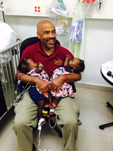 Henri Ford, MD, CHLA's Haitian-born surgeon in chief, holds recently separated conjoined twins Marian and Michelle Bernard three days after Ford led an international team in Haiti to perform the rare surgery, a first in the Caribbean country. CHLA sent a medical team of 18 to conduct the operation. (Photo: Business Wire)