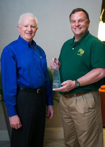 Lee Clarke, senior account executive at Tyler Technologies, presents a Tyler Excellence Award to John Brockwell, director of technology at Prince George County Public Schools, Virginia. (Photo: Business Wire)