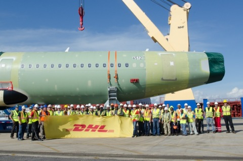 Members of DHL Global Forwarding, Airbus, the International Longshoremen's Association (Local 14010) and AMP Terminal employees pose in front of the fuselage of the first Airbus A320 aircraft to be assembled at the Airbus U.S. Manufacturing Facility in Mobile, Alabama. (Photo: Business Wire)