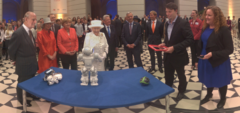"""Panono executives meet with German Chancellor Angela Merkel and the Queen of England on the 50th Anniversary of the """"Queen's Lecture"""" at the Technical University of Berlin. The Panono Camera was one of only two technology projects demonstrated at the event. (Photo: Business Wire)"""