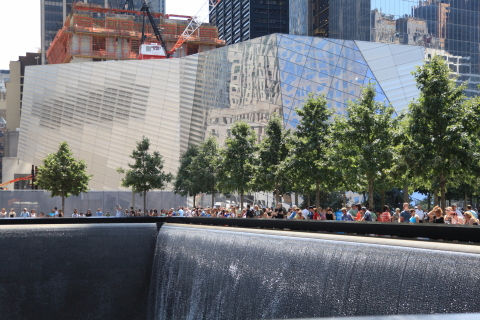 Visitors at a reflecting pool and waterfall, one of two set within the footprints of the original Twin Towers, are part of the National September 11 Memorial & Museum (museum in the background) honoring the victims and heroes of terrorist attacks on the United States. Accenture developed the technology network for the digital exhibits that span three floors below ground. Photo credit Amy Dreher, 9/11 Memorial