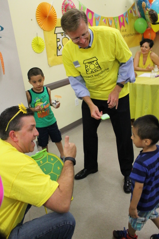 Michael McGuire, CEO of UnitedHealthcare of New York (right), and David Milich of UnitedHealthcare of Texas cheer on one of the children at Project Sunshine's beach party at EHACE (East Harlem Asthma Center of Excellence) (Photo: Project Sunshine).