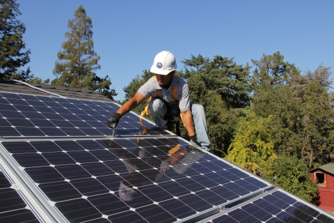 An installation specialist adjusts Quick Mount PV's Quick Rack rail-free rack system in this residential installation of SolarWorld solar panels in Alamo, California. (Photo: Business Wire)