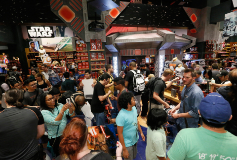 Fans enjoy midnight madness as Force Friday kicks off at Disney Store in New York's Times Square, Friday, Sept. 4, 2015, to celebrate the launch of merchandise for Star Wars: The Force Awakens. (Photo by Stuart Ramson/Invision for Disney Consumer Products/AP Images)