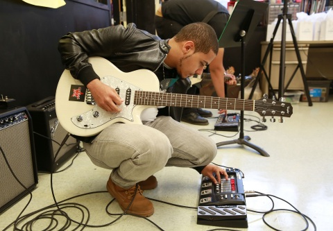 Adam Saleh, student at at Juan Morel Campos Secondary School in Brooklyn, NY, tunes his guitar befor ...