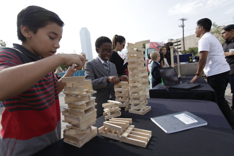 Children tinker with learning toys during a TECH Truck stop. (Photo: Business Wire)