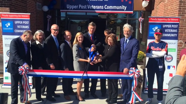 Newly moved-in veterans join Congressman Erik Paulsen and project partners in cutting a ceremonial ribbon to celebrate the opening of Upper Post Veterans Community, a 58-unit affordable-housing community at Fort Snelling (Video: Greg Page).