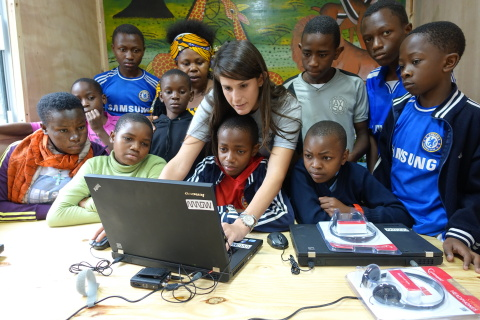 Children from the Tuleeni Orphanage in Tanzania learn to use the new computers in their mobile classroom with help from Neema International founder and executive director Mandy Stein. (Photo: Business Wire)