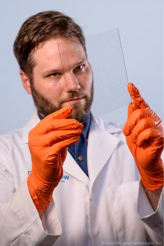 SolarWindow Principal Scientist Dr. Scott Hammond inspects invisible wire microgrid in SolarWindow e ...