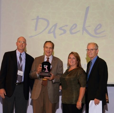 """Daseke CEO Don Daseke (second from left) accepts the Owens Corning supplier of the year award in its """"sustainability"""" category from Owens Corning executives at the company's annual supplier recognition event. Owens Corning works with a supplier base exceeding 10,000 worldwide, and Daseke was the only trucking company honored with an award. From left to right are: Tony Heldreth, vice president of supply chain; Daseke; Amy Mielke, transportation sourcing leader; and Frank O'Brien-Bernini, vice president and chief sustainability officer. (Photo: Business Wire)"""