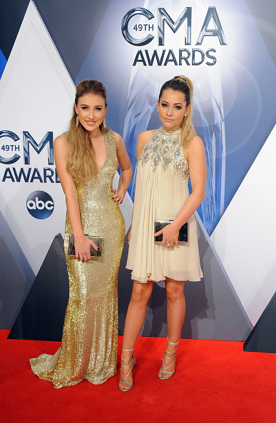 """Maddie & Tae carry Jill Milan Art Deco Clutches at the 49th annual CMA Awards, Nov. 4, 2015 in Nashville, Tenn. Maddie & Tae won at the Country Music Awards in the Music Video category with their debut video for """"Girl in a Country Song."""" (Photo: Jon Kopaloff, FilmMagic)"""
