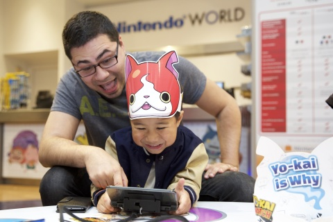 In this photo provided by Nintendo of America, David C. and son Dylan C., 4 years old, from Forest Hills, New York, play the YO-KAI WATCH game for the Nintendo 3DS family of systems at the Nintendo World launch event in New York on Nov. 7, 2015.