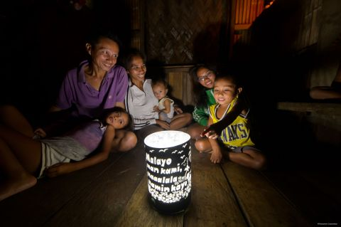 Family gathering around the solar lantern with a handmade shade (Photo: Business Wire)