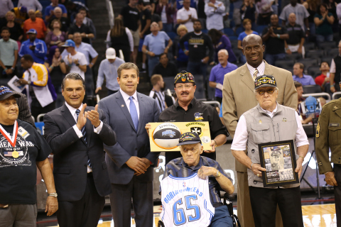 """Members of the U.S. Army 65th Infantry Regiment """"Borinqueneers"""" were honored last night by representatives from Harris Corporation and the Orlando Magic. Harris and the Magic provided 500 tickets to members of the military and recognized veterans during special programs throughout the Veterans Day game at the Amway Center in Orlando. Pictured with members of the Borinqueneers include Orlando Magic CEO Alex Martins (second from left), Harris HR and Administration SVP Bob Duffy, and Magic Community Ambassador Bo Outlaw (back far right). (Photo: Business Wire)"""
