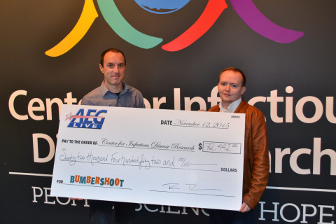 Rob Thomas (left), vice president of AEG Live Pacific Northwest, presents Edward Jenkins from the Center for Infectious Disease Research with a fundraising check from Bumbershoot 2015. (Photo: Business Wire)