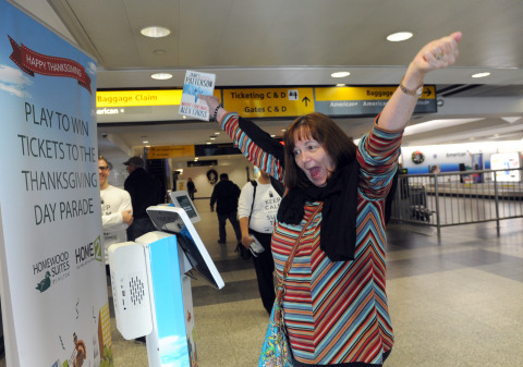 Sally Maxey, a teacher from Graham, Texas, reacts as she wins free tickets to the Thanksgiving Day Parade courtesy of Homewood Suites by Hilton as she leaves New York's LaGuardia Airport (Photo by Diane Bondareff/AP Images for Homewood Suites by Hilton)