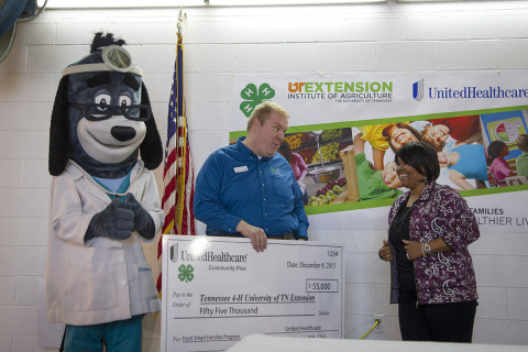 "(L-R) UnitedHealthcare Mascot Dr. Health E. Hound joins Justin Crowe, University of Tennessee 4-H Extension as he accepts a $55,000 check from Rita Johnson-Mills, CEO, UnitedHealthcare Community Plan of Tennessee to support the ""4-H Food Smart Families"" program. The partnership was announced at the Agricenter Farmer's Market in Memphis, Tenn. where 4-H youth and community leaders participated in multiple training sessions to learn about food – how to secure it, use it and cook it, and make choices that enhance their health and well-being. (Photo Credit: Lisa Buser)"
