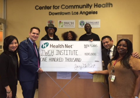 Carol Kim, Health Net's director of Public Affairs (left), presents $100,000 check to the staff of JWCH Institute to help house homeless patients. From the left are: Dr. Paul Gregerson, chief medical officer; Chris Mack, outreach worker; Linda Evans, case manager; Shawn Baker, case manager; Al Ballesteros, CEO; and Cheryl Morris, case manager. (Photo: Business Wire)