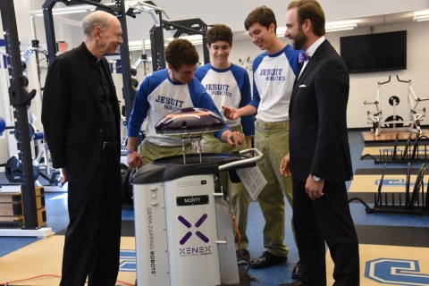 """Rev. Anthony McGinn and members of the Jesuit High School of New Orleans Robotics Club welcome """"Morty,"""" a Germ-Zapping Robot and gift from Jesuit alumnus Joseph Authement, SVP of Xenex. Morty will wage environmental war by destroying bacteria and potentially deadly pathogens typically found lurking inside gymnasiums, athletic locker rooms, weight training areas, shower and bathroom facilities, and even personal sports equipment. (Photo: Business Wire)"""