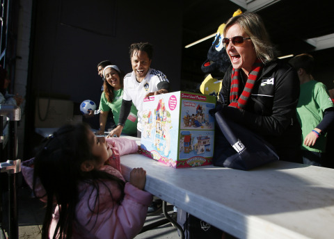 Herbalife employees hand out toys at A Place Called Home's annual toy distribution event. (Photo: Business Wire)