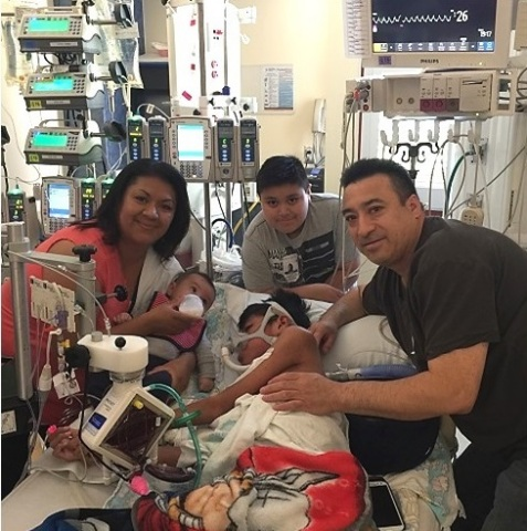 2015 was a year of dramatic changes for Oswaldo and his family, seen here at his bedside, post-transplant surgery in July. (Photo: Business Wire)