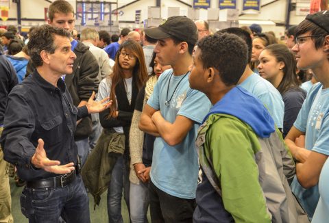 "FIRST® Founder Dean Kamen and FIRST® Robotics Competition Team 1289, ""Gearheadz"" from Lawrence, Mass., talk excitedly at the Kickoff event in Manchester, New Hampshire – where more than 1,000 attendees gathered for the 2016 game reveal of FIRST STRONGHOLD. (Photo: Business Wire)"