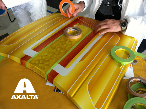 Artists in action preparing a hood for pinstriping - the art of applying very thin lines of paint to decorate a surface or create special graphics most commonly found on automobile and motorcycle bodies. (Photo: Axalta)