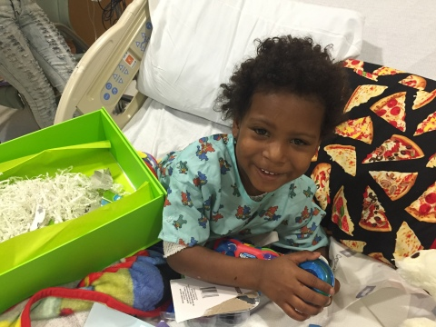 A young patient at UNC Children's enjoying a Cheeriodicals Big Green Box of Cheer from LabCorp. (Pho ...