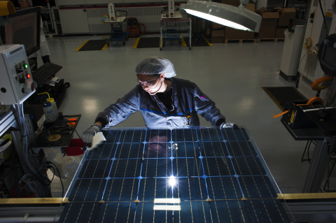 A worker at SolarWorld Americas Inc., based in Hillsboro, Oregon, inspects a bifacial Bisun laminate before it is framed to become a two-sided solar panel in the company's first production run of the new technology. Bisun solar technology captures both direct solar radiation on its front side as well as indirect sunlight on its back side, producing up to 25 percent more energy than standard solar panels of the same nominal wattages. This panel was among shipments for a system at the University of Richmond in Virginia. (Photo: Business Wire)