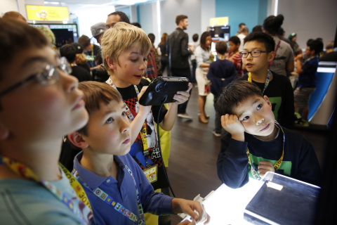 In this photo provided by Nintendo of America, kids gather at The Mix at San Francisco Public Library's Main Library location in Downtown San Francisco to attend a workshop that taught the basics of video game level design using the Super Mario Maker game for the Wii U console. With the help of Nintendo experts, attendees designed and played through their own Super Mario Bros.-themed levels by leveraging the creative tools available within the Super Mario Maker game. (Alison Yin/AP Images for Nintendo of America)