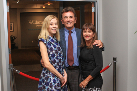 "Dr. Eugene Skourtes (center), his wife, Bonnie (right) and Paige Powell (left), prepare to unveil Jean-Michel Basquiat's ""The Back of the Neck"" at the cultural arts initiative event at the company's headquarters in Hillsboro, Ore. March 28 (Photo: Business Wire)."