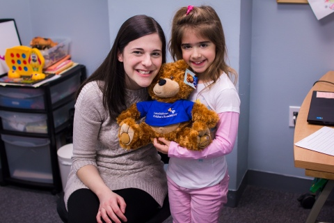 Penelope and her speech therapist Samantha Wallace share a smile with Oliver the Bear (Photo: UnitedHealthcare Children's Foundation).