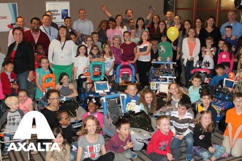 Axalta employees and their children pose with a few of the modified, motorized cars they built for GoBabyGo! families. (Photo: Axalta)
