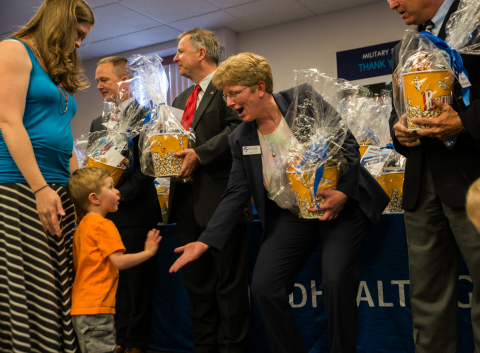 """(L-R) Military spouse Lindsay Kester and son Elias, 3, receive a high-five from Kate Hatten, president and CEO, Peak Military Care Network, along with one of the 250 """"Family Movie Night"""" gift baskets that were distributed as part of Military Spouse Appreciation Day in Colorado Springs, Colo. Also pictured l-r: Tom Wiffler, chief operating officer, UnitedHealthcare Military & Veterans, and U.S. Congressman Doug Lamborn (R-Colo.) (Photo: Teresa Lee)."""