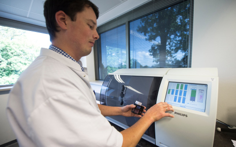 Lab technician inserts tissue slide rack into the Philips IntelliSite ultra-fast scanner (Photo: Business Wire).