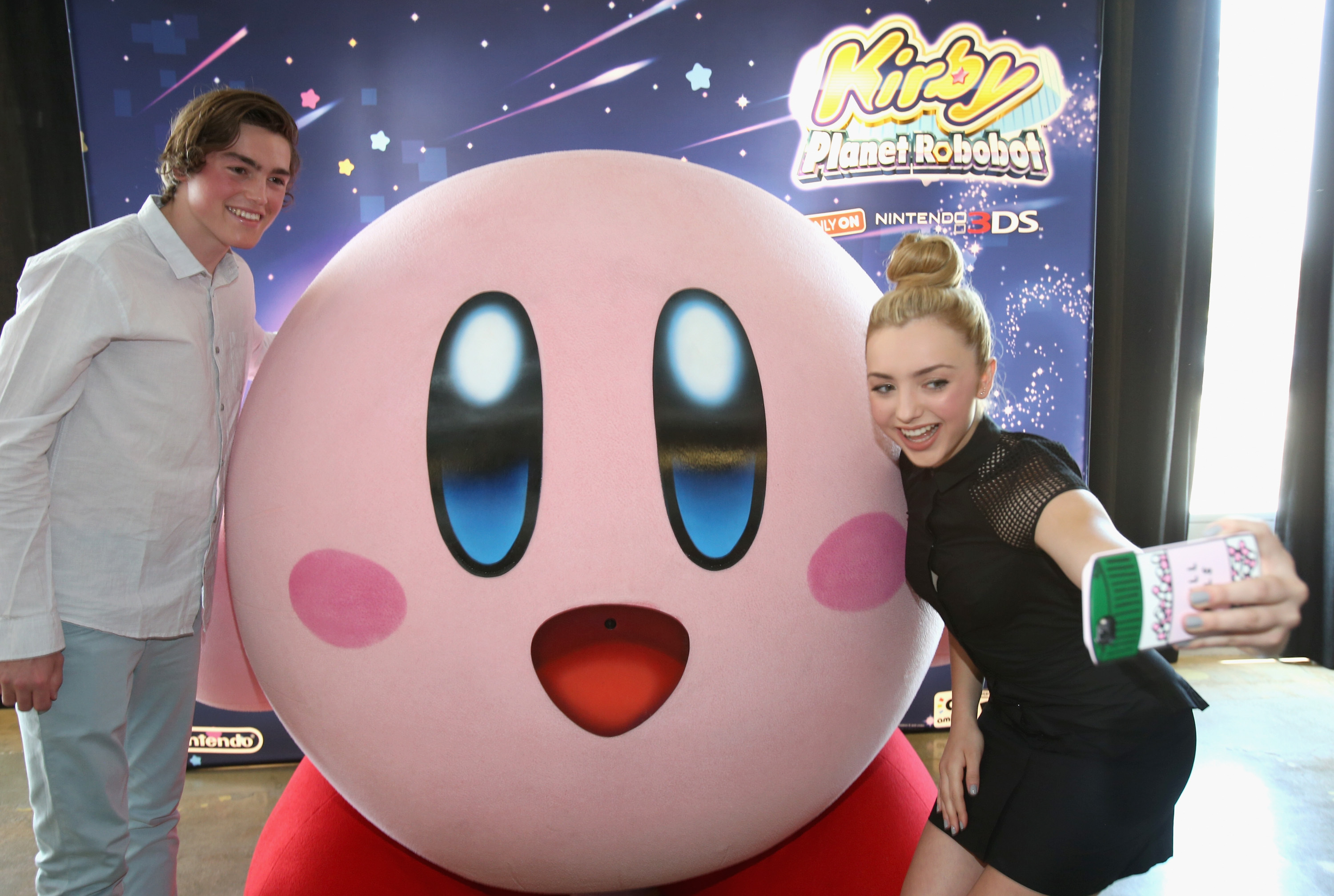 """In this photo provided by Nintendo of America, Peyton List from Disney's """"Bunk'd' who is starring in the upcoming feature """"The Thinning"""" and Spencer List from """"The Bachelors"""" interact with Kirby at the Kirby: Planet Robobot celebration at Smashbox Studios in Culver City, California, on June 22, 2016. Kirby: Planet Robobot, the latest instalment in the popular franchise, available now for the Nintendo 3DS family of systems."""