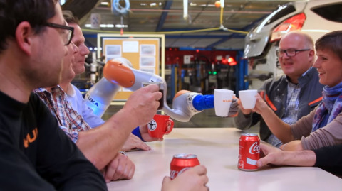 Ford Motor Company workers use collaborative robots, also known as co-bots, to help fit shock absorbers to Fiesta cars in Cologne, Germany. The co-bots ensures perfect fit, and help workers avoid having to access hard to reach places on the assembly line. (Photo: Business Wire)