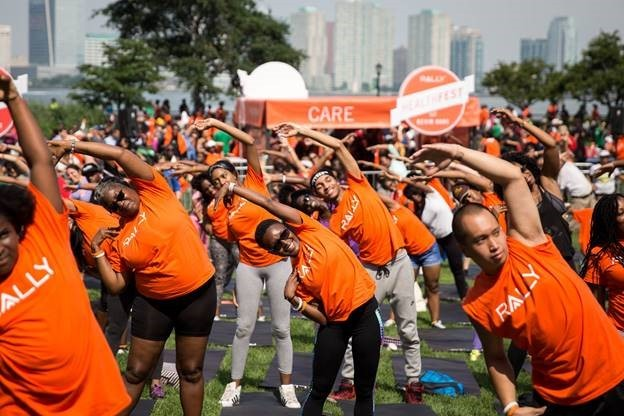 """More than 10,000 people joined Rally Health, actor/comedian and Rally Health Ambassador Kevin Hart, and E! News host Maria Menounos at the Rally HealthFest today in Nelson A. Rockefeller Park in Battery Park City. This free event was held to show the community how making simple lifestyle changes can be fun and help improve one's overall health. Here, New Yorkers participate in a group exercise led by Ron """"Boss"""" Everline, Kevin Hart's Trainer. (Photo: Business Wire)"""