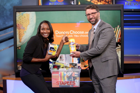 Bill Durling, vice president, global communications for Staples (left) presents Genein Letford, a teacher at New Academy Elementary School in Canoga Park, Calif. (middle) with a package of school supplies for her students, courtesy of Staples, during KCAL 9's News at Noon Thurs., Aug. 4, 2016, in Los Angeles. (Photo by Casey Rodgers/AP Images for Staples)