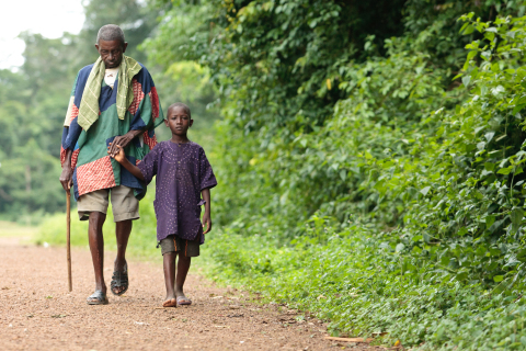 A boy helps Samuel Nicol (age unknown), who was blinded by river blindness, walk through the village of Gbonjeima, Sierra Leone, on Saturday, July 14, 2012. The Task Force for Global Health is working with partners to eliminate river blindness by 2025. Copyright: Olivier Asselin, courtesy of the Global Network for Neglected Tropical Diseases.