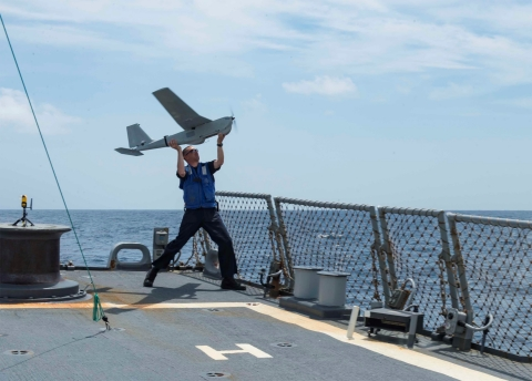 An operator launches the RQ-20B AeroVironment Puma AE System from the USS Stout during precision rec ...