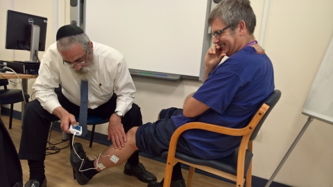 Dr. Graham Bowen, Head of Podiatry & Clinical Services Manager at Solent NHS Trust in Southampton UK trying out FlowAid's FA100 SCCD. Jacob Brezel, CEO, at left operating the device. (Photo: Business Wire)