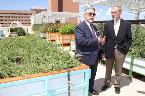 Chris Baca, CEO, YES Housing (left) and Charles Milligan, CEO of UnitedHealthcare Community Plan of New Mexico tour the rooftop community garden at the Imperial Building, a new 74-unit mixed-use apartment community in downtown Albuquerque. UnitedHealthcare is the largest investor in the development, providing $11.9 million in equity, part of $34 million the company has invested in building affordable housing communities in the state (Photo: Jessica Quinn).