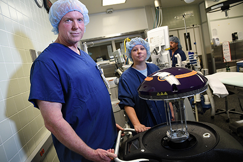 Sharp Coronado Hospital has deployed a Xenex Germ-Zapping Robot to destroy germs and bacteria lurking in the hospital that can pose a risk to patient safety. Pictured with the robot are Stephen Decker, general manager of environmental services, and Lindsay Schimpf, RN, CCRN, infection preventionist Sharp Coronado Hospital. (Photo: Business Wire)