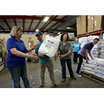 Pictured here, PetSmart, PetSmart Charities and Pima Animal Care Center (PACC) representatives, as well as DOG for DOG founder and CEO Rocky Kanaka unload a recent shipment of 300,000 DOG for DOG meals to support pets in need in the Tucson area -- completing the one million-plus meal donation across the continent. The donation to PACC will provide meals for more than 20,000 dogs and allow the shelter to use its annual food budget of $80,000 to provide other services. (Photo: Business Wire)